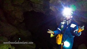 A Cave Opening of Brown Rock With a Man Standing on the Right of the Opening in Dark Blue Coveralls and a Helmet With a Headlight Turned On