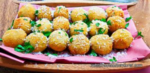 Three Rows of Croquettes on a Piece of Pink Butcher Paper on a Wooden Tray Sprinkled With White Cheese and Garnished With Fresh Parsley