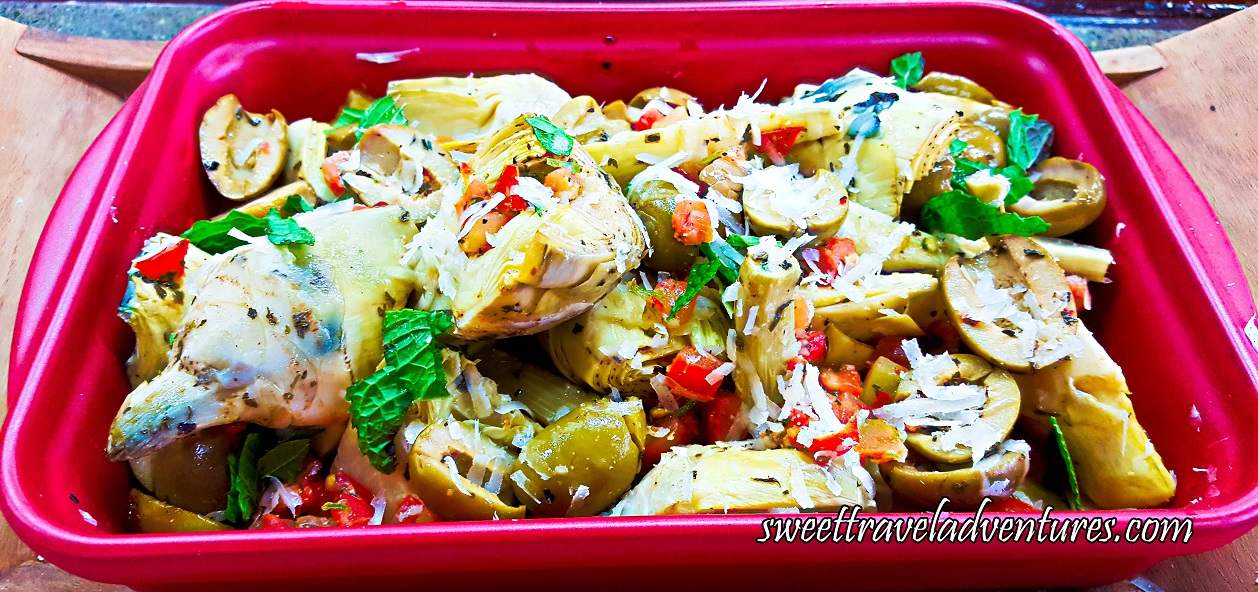 A Large Pink Dish of Artichokes With Mint, Tomatoes, and Olives on a Wooden Tray