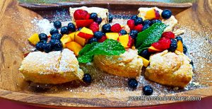 Tarts on a Wooden Tray and Topped With Fresh Peaches, Blueberries, and Raspberries, as well as a Couple Mint Leaves, Drizzled With Honey, and Sprinkled With Icing Sugar