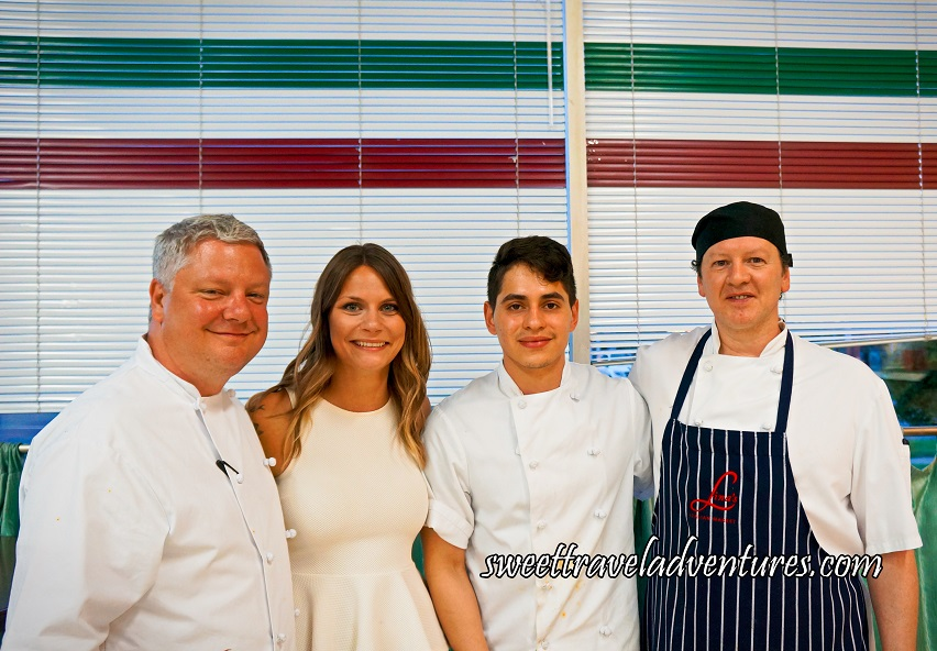 A Man, A Woman, and Two Men All Standing in Front of White Blinds With a Red, White, and Green Stripe at the Top (Like the Italian Flag), the Men are Wearing White Chef Jackets and the Man on the Far Right is Wearing a Black and White Vertically Striped Apron on Top of His Chef Jacket, and the Woman is Wearing a White Sleeveless Blouse