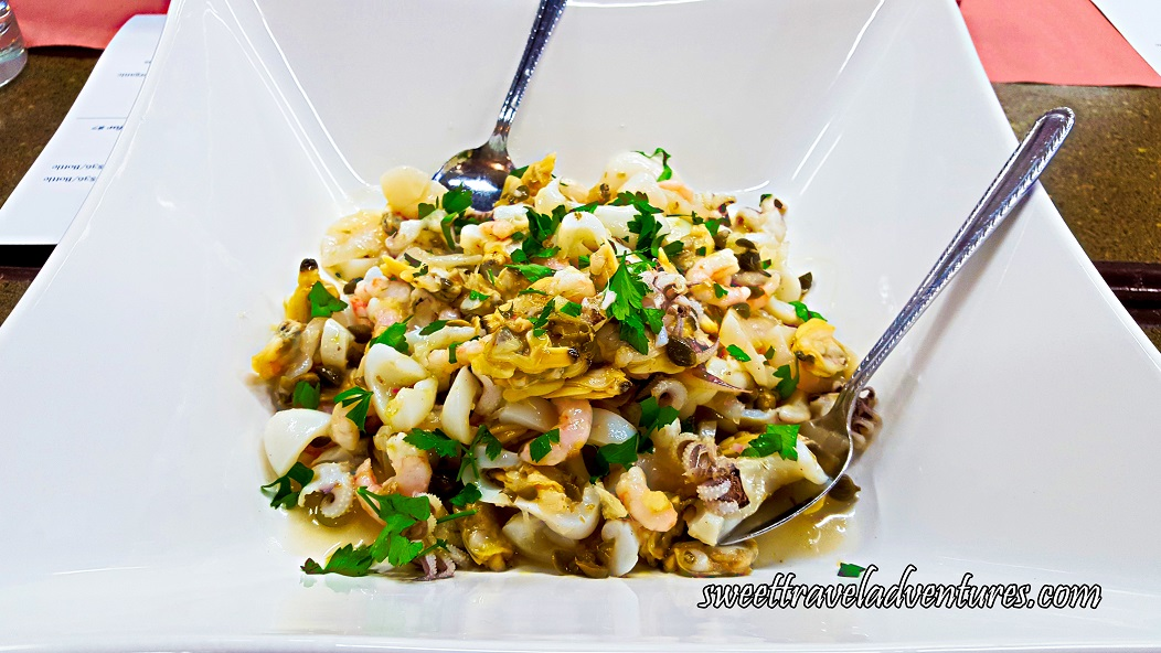 Shrimp, Squid, Clams, Mussels, and Slices of a White Fish With Parsley and a Little Dressing on the Bottom of a White Dish and a Silver Spoon on Either Side of the Dish