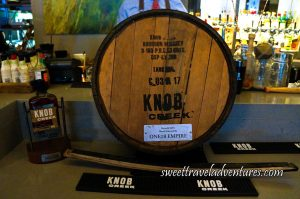 The Bottom of a Wooden Barrel Sitting on a Grey Bar Stamped in Black Ink and a Metal Label, in Front is a Piece of the Side of the Barrel, on the Left is a Bottle on a Stand, and Bottles and Mixology Equipment Behind