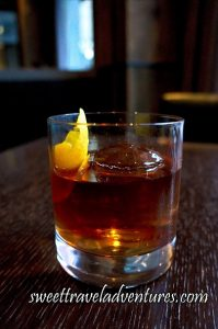A Drink in a Short Glass Sitting on a Dark Wooden Table With the Top of an Ice Sphere Sticking Out of the Golden Brown Liquid and the Top of a Twisted Orange Rind Sitting Vertically in the Glass and Also Sticking Out of the Liquid