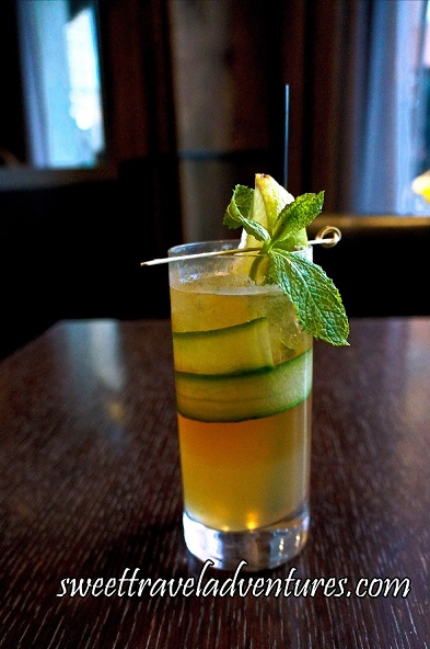 A Drink in a Tall Glass on a Dark Wooden Table With a Golden Yellow Liquid and Strip of Cucumber Around the Top Inside of the Glass, A Metal Pick Sitting on the Top of the Glass With a Mint Leaf, and a Lemon Wedge Sticking Out of the Top of the Glass Along With a Long Black Straw Behind it