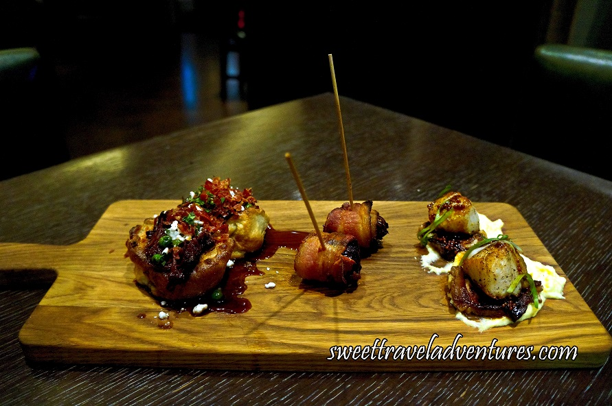 A Wooden Board on Top of a Dark Wooden Table With Two Yorkshire Puddings on the Left (Placed Vertically) Topped With Bourbon Short Ribs, Smashed Peas, and Goat Cheese With Pancetta, Mint, and Gravy, Two Dates Each Wrapped in Bacon and Pierced With a Long Wooden Pick, and Two Seared Diver Scallops On Top of Pork Belly, Creamy Polenta, and Mustard Jus