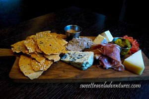 A Wooden Cutting Board on a Dark Wooden Table With Crispy Crackers on the Left, Next From Top to Bottom a Small Metal Container With Mustard Seed, Pork Rillettes, and Blue Cheese, Next is Canadian Brie Behind and Proscuittio in Front, Next is a Small Metal Container With Sliced Pickles, Next is Calabrese Salami Behind and Oka Cheese In Front