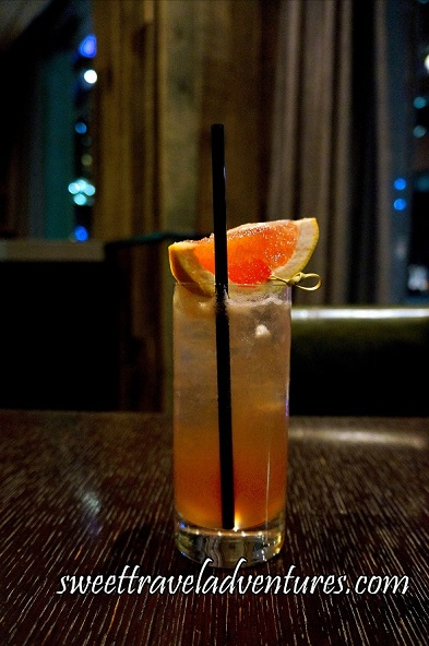 A Drink in a Tall Glass Sitting on a Dark Wooden Table With a Dark Brown Leather Chair Behind and in the Distance Partial View of Two Windows With Tan Curtains at the Side and Darkness and Lights Reflecting in, the Drink is Peach Coloured on the Bottom and the Top Half is Clear With Lots of Ice and Topped With a Grapefruit Wedge With a Gold Metal Pick Through it and Long Black Straw