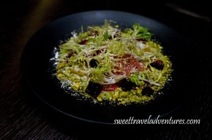 Black Plate With a Green Salad With Golden. Striped, and Red Beets and a Dusting of White