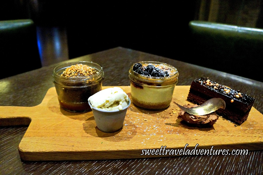 A Light Wooden Cutting Board on a Dark Wood Table With a Small Jar on the Left With a Round Brown Cake Topped With Nuts and a Brown Sauce on the Bottom of the Jar, Next on the Right and Slightly in Front is a Small Greyish Container Filled With Vanilla Coloured Ice-Cream, to the Right and Slightly Behind is a Small Glass Jar With a Small Section of Brown on the Bottom, Mostly Filled With Something Cream Coloured, and on Top is a Thin Brown Section With Cherries on One Side, to the Right and Slightly in Front is a Brown Mousse With a Gold Leaf on Top, and to the Right and Slightly Behind is a Layered Chocolate Cake With a Layer of Light Brown, a Layer of Dark Brown, and a Layer of Light Brown, With a Dark Brown Glaze on Top and Sprinkled With Small Balls of Different Colours