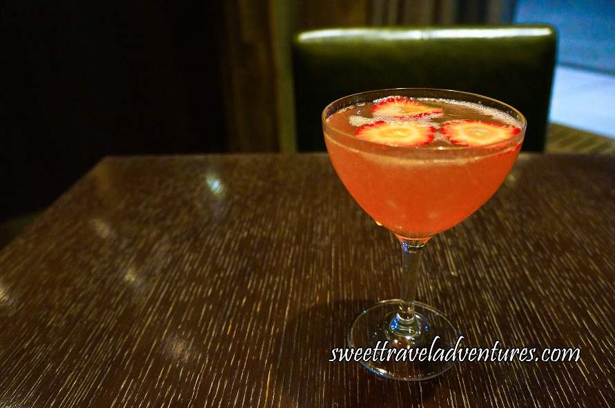 A Drink in a Cocktail Glass Sitting on a Dark Wooden Table With a Dark Brown Leather Chair Behind and a Portion of a Window on the Right With the Road and Sidewalk, the Glass is Filled With a Peachy Pink Liquid and Floating on Top is Three Slices of Strawberry