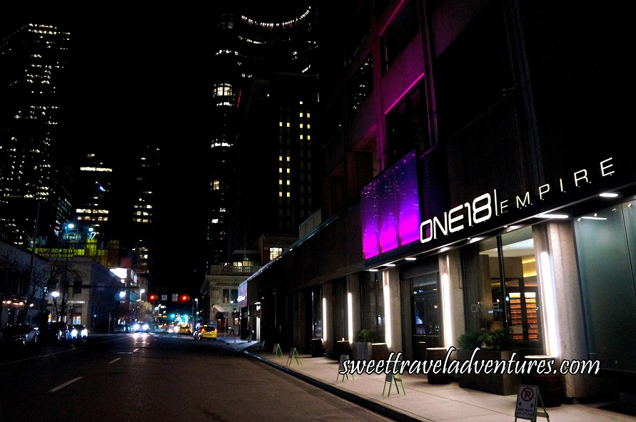 One18 Empire on the Right Next to a Sidewalk and Street (A Black Building With White Lettering and White Columns and a Few Rectangles Lit up in Raspberry and Purple), Short White Buildings Next to it, and Tall Office Buildings With a Few Lights on in the Background