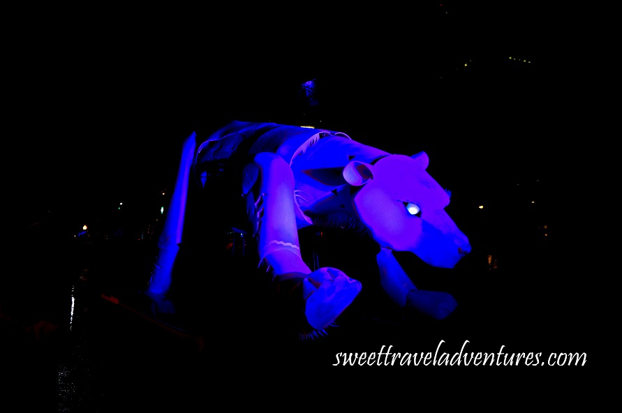 Giant Polar Bear Puppet on the Street at Night Lit a Dark Blue Colour With a Little Bit of Purple