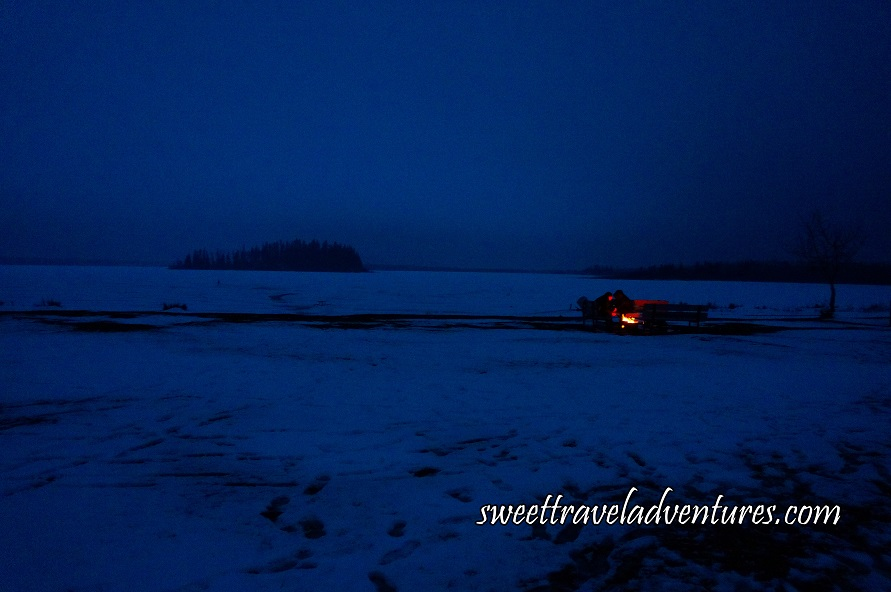 A Couple at a Campfire at Dusk With Snow Around Them and Trees in the Background and a Dark Blue Sky