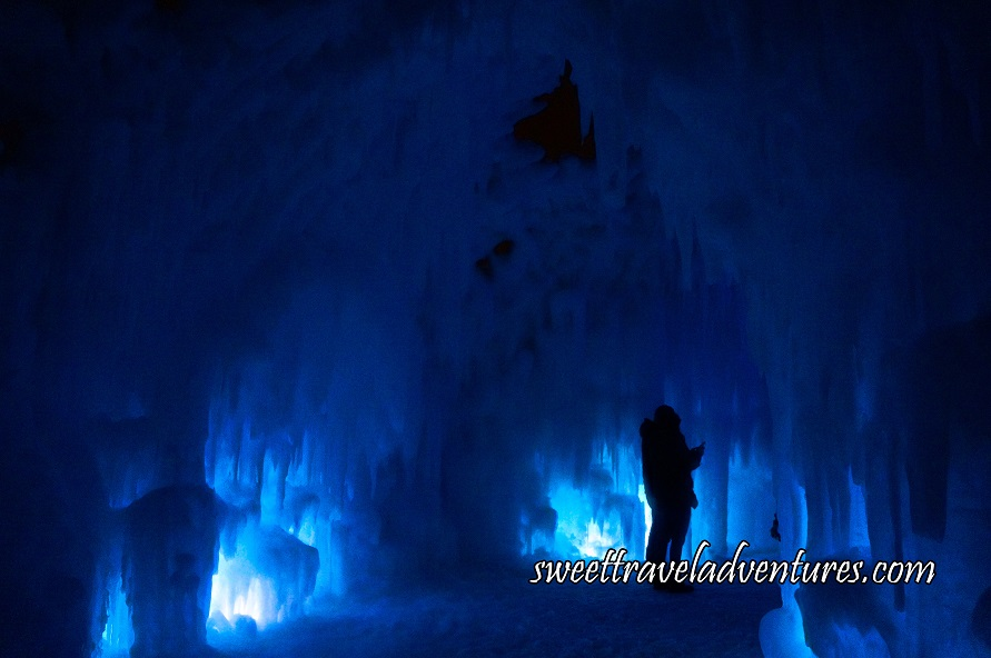 A Silhouette of a Couple Taking a Selfie in an Ice Cavern Partially Illuminated a Lighter Blue at Night