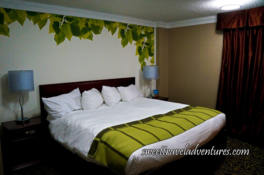 A Bed With a Cherry Wood Frame and Night Tables Next to it With White Lamps, the Sheets on the Bed are White and a Bright Green Blanket on the Lower Portion of the Bed, a White Wall With Rich Green and Bright Green Leaves Bordering it, on the Right is a Tan Coloured Wall With Reddish Brown Satin Curtains, and a Patterned Carpet