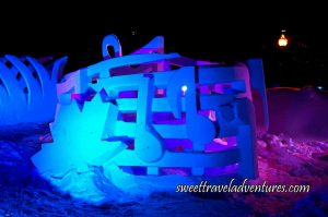 A Snow Sculpture of Musical Notes and a Large Maple Leaf on the Left, All Lit Up at Night With Blue and Purple Lights