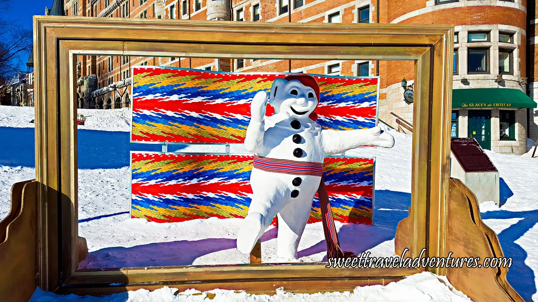 A Wooden Picture Frame With a Snowman Mascot Standing and Waving Inside the Frame Wearing a Red Tourque and a Colourful Sash, Directly Behind is Two Large Pieces of Material Like the Sash, in the Background is a Large Hotel, and the Ground is Covered in Snow