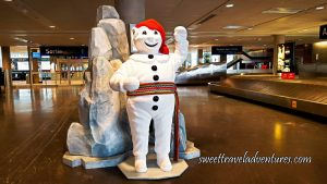 At an Airport is A Mascot Statue of a Snowman Wearing a Red Touque and Multi-Coloured Sash Around its Waist and Giant Rocks Behind it, on the Right is a Baggage Carousel, and Behind in the Distance is Glass Exit Doors