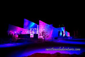 A Contemporary Style Ice Structure at Night Lit Up With Pink and Dark Blue Lights Behind a Short Metal Fence, a Tree in the Center, the Ground Covered With Snow and More Snow Piled Up Around the Structure Also Lit Up Pink and Dark Blue