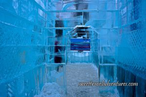 A Corridor With Ice Walls and a Doorway Looking Through to Another Room and Directly at a Painting Hanging on the Ice Wall