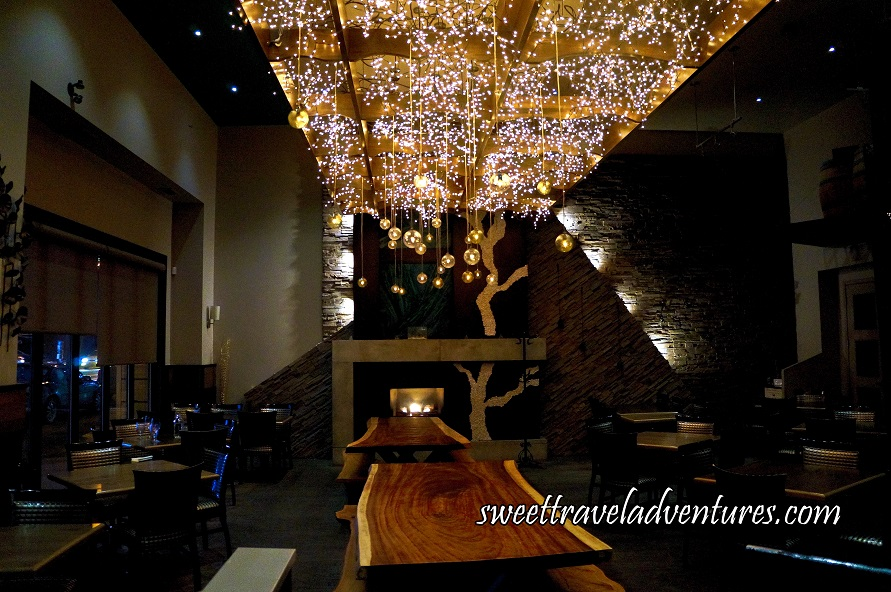 A Room With Two Long Wooden Tables in the Middle With Many Tiny Lights Hanging Above and Some Hanging Balls With Lights Inside, a Fireplace With Stone Lit in Front of Them, on Either Side Dark Wooden Tables With Matching Wooden Chairs With Metal Embellishments and Glass Windows on the Left
