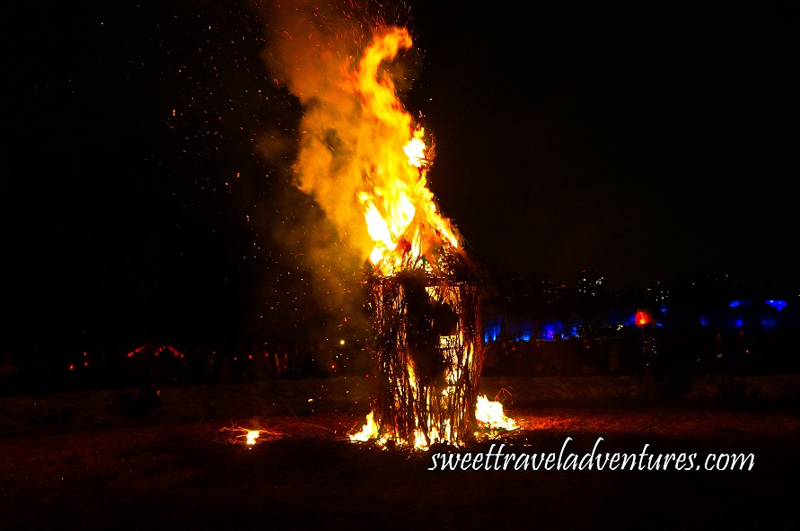 A Wooden Structure Burning at Night With Large Flames and Smoke on the Upper Portion and Some Sparks