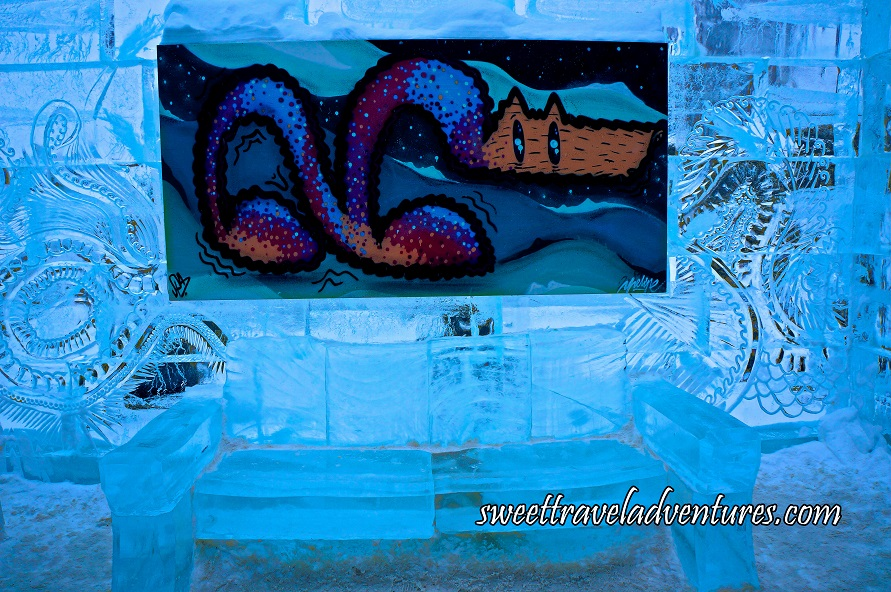 An Ice Wall With Intricate Designs With a Painting Hanging on it and a Bench Made of Ice Below and the Ground Lightly Covered in Snow