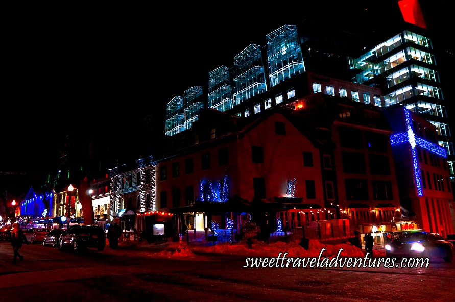 A Street at Night With the Buildings Lit Up With Dark Blue, Green, White, or Red Lights, and a Building With Lights That Make It Look Like it is Partially Wrapped With Dark Blue Ribbon With a White Snowflake Bow