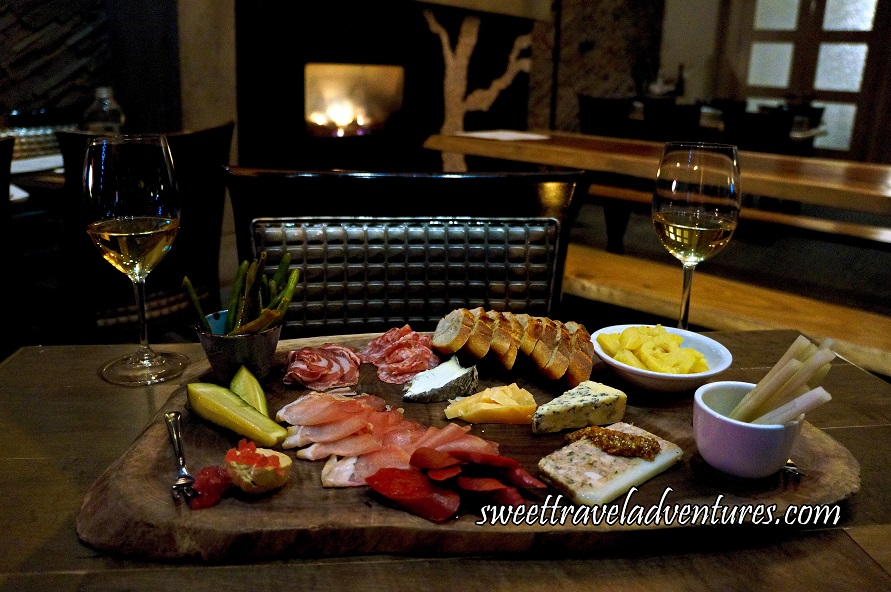 A Wooden Board Sitting on a Wooden Table With a Variety of Meats, Cheeses, Pickled Vegetables and Beans, and Slices of Bread With A Glass of White Wine on Each Side of the Board, and a Lit Fireplace in the Background