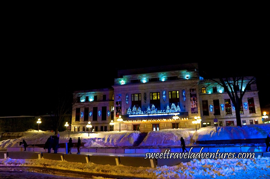 An Outdoor Ice Rink at Night With a Few Ice Skaters, Snow Piled Up Around the Rink, Behind it a Tree on the Right and One on the Left and Further Behind a Large Building With Decorative Lights Lit Up