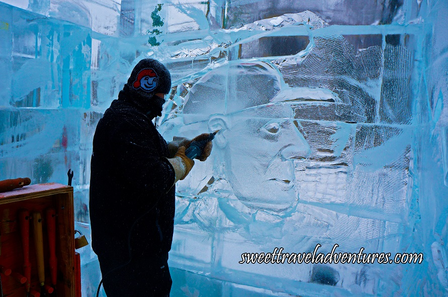 A Man With a Black Winter Coat and a Black Touque Using a Tool to Shape the Ears of a Man Wearing a Baseball Cap Whose Face and Head is Etched Into an Ice Wall, a Wooden Box With Tools Hanging Inside it to the Left of the Ice Sculptor