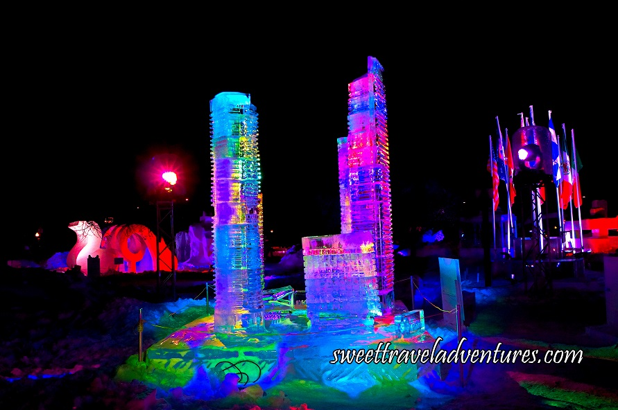 Ice Sculpture of Skyscrapers Lit Up at Night With Multiple Coloured Lights, in the Background on the Right is Several Poles With Flags and on the Left is a Snow Sculpture Lit Up