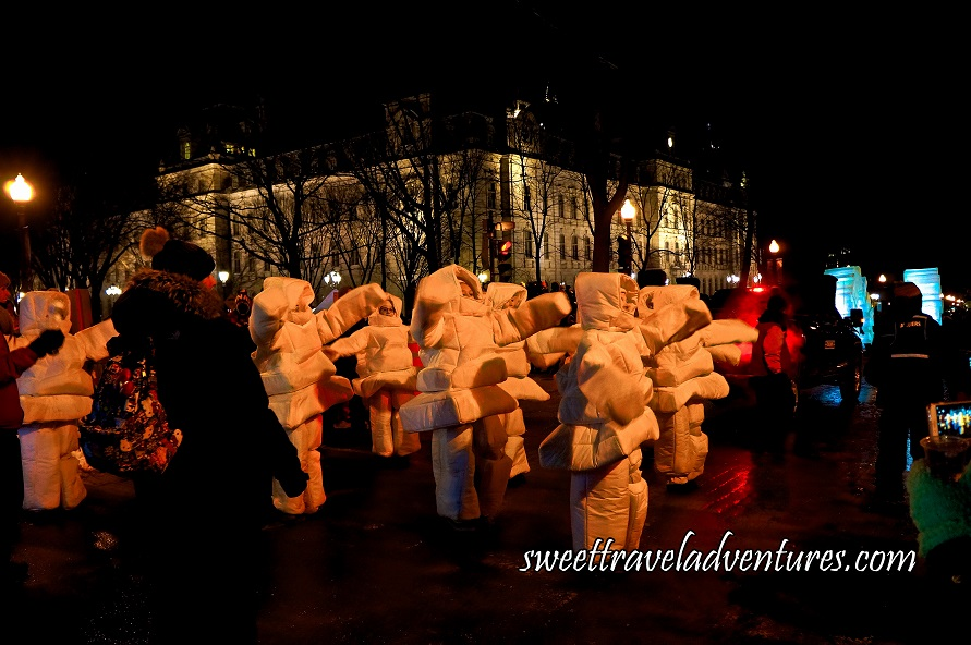People Dressed as Inukshuks on the Street at Night With a Building Illuminated in the Background