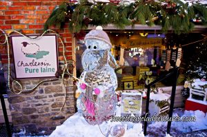 A Lamb Ice Sculpture Wearing a Tan Touque and Holding Knitting Needles and a Half Knit Tan and Pink Scarf, Standing in Front of a Brick Building With a Large Glass Window Looking Into a Store With Items on Display and Green Garland Hanging Above the Window, and a Tan Coloured Square Store Sign to the Left of the Window Hanging from the Brick Building Which Has Orange Brick on the Upper Half and Light Brown Brick on the Lower Half