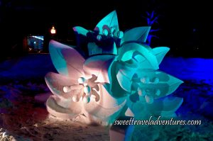 A Snow Sculpture of a Group of Three Maple Flowers at Night Lit Up With a White Light, a Green Light, and a Little Bit of Purple Light, Behind the Sculpture is Dark Blue Lights on the Snow. and a Building in the Background on the Left