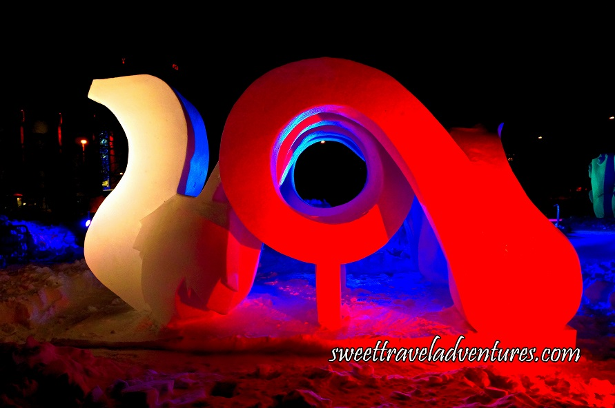 A Snow Sculpture at Night That Looks Like a Vertical Squiggle With a White Light on it Attached to a Circular Structure With a Piece That Leads Downwards and is Lit Up With a Red Light, and Snow Underneath the Sculpture and Behind it