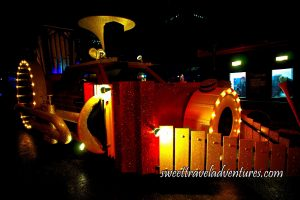 A Red Truck With Red Sparkles on the Street at Night Made to Look Like a Train, on the Front is a Yellow Drum With Lights Around it and Around the Drum Are Two Yellow Xylophones Forming a Triangular Shape on the Front of the Train, a Yellow Horn Sticking Out the Top, a Yellow Trombone Along the Side of the Train With Lights Lit Up Around the Circular Part of the Instrument, a Yellow Organ Sticking Out the Back, and a Structure on the Other Side of the Street With Lights on and People Inside the Two Windows on the Right