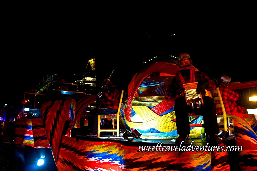 A Float at Night with Musicians Sitting on Wooden Chairs Playing Music Dressed With Red and Black Checkered Jackets and Black Pants, a Giant Ball on One End of the Float With Different Colours of Fabric Wrapped Around it, and the Arrowhead Sash Wrapped Around the Bottom of the Float