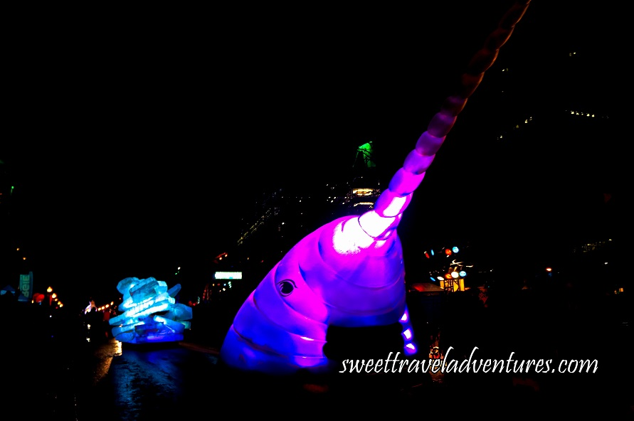 A Float on the Street at Night Shaped Like the Head of a Narwhal and Lit Up With Purple Lights and a Little Bit of Dark Blue Light, Following Behind is an Iceberg Float Lit Up With Turquoise and White Lights, in the Background are Buildings With Only a Few Lights on
