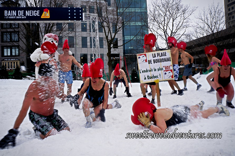 People in Their Bathing Suits Wearing Giant Red Rooster Hats Dancing or Playing in the Snow, a Couple People Hugging Bonhomme, and a Woman Lying Face Down in the Snow
