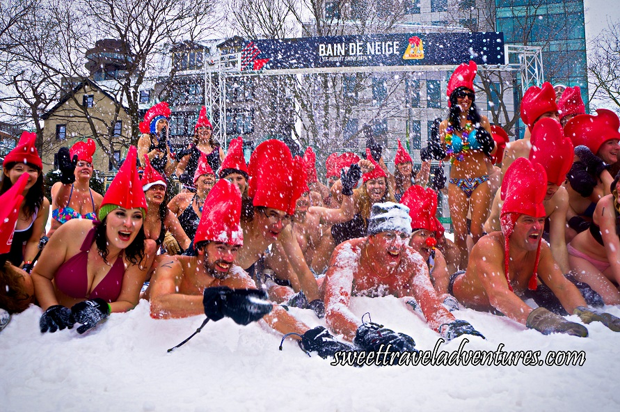 People in Their Bathing Suits Wearing Giant Red Rooster Hats Lying Down in the Snow and a Few People Standing Up Behind