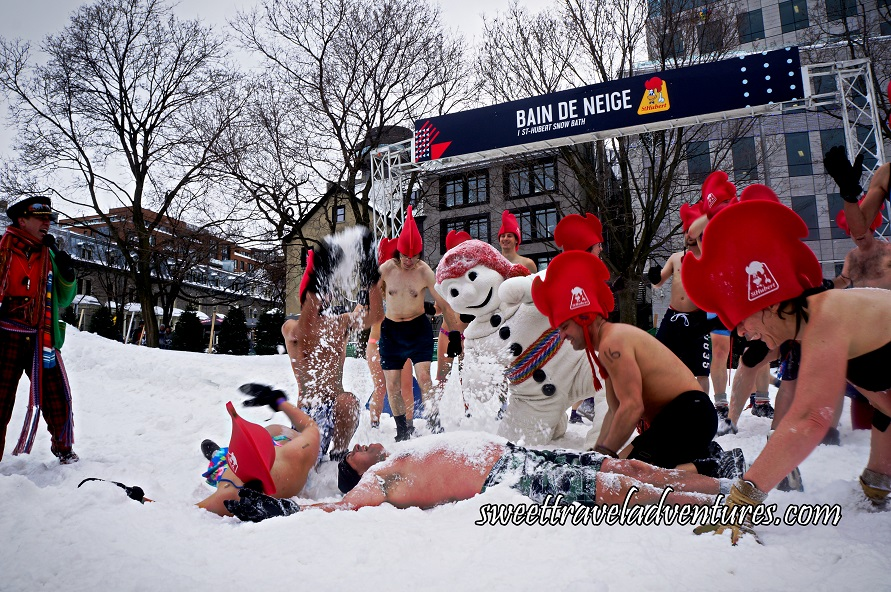 People in Their Bathing Suits Wearing Giant Red Rooster Hats Playing in the Snow With Bonhomme and Some People Lying and Rolling Around in the Snow