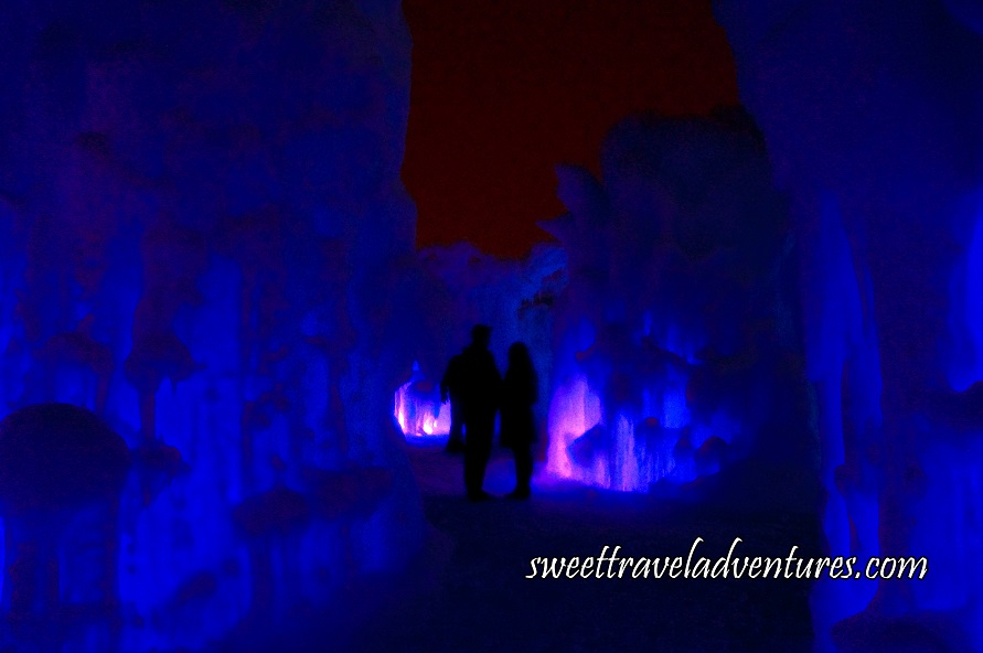 A Silhouette of a Couple Standing on a Snowy Path With Blue Frozen Ice Structures Lining the Path and in Front of Them, and the Ice Structure in Front of Them and to the Right Partially Illuminated Pink and the Night Sky Above
