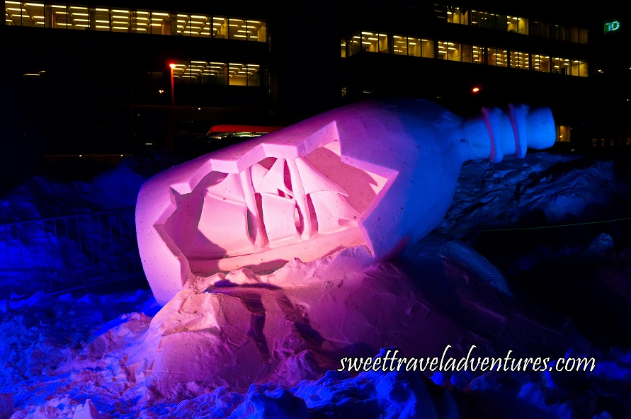 A Snow Sculpture of a Bottle Tilting Upwards to the Right on the Snow With the Front of the Bottle Cut Out and a Large Ship Showing Inside With Pink Light on the Bottle and Some Dark Blue Light, and Around it Dark Blue Snow, in the Background a Large Building With the Lights on Inside
