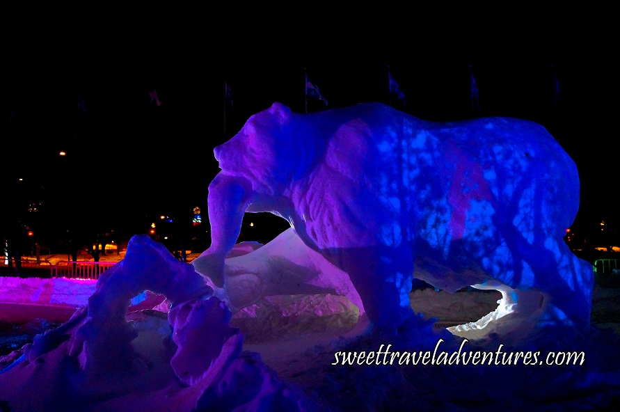 A Snow Sculpture of a Large Bear Holding a Fish in its Mouth and Some Pink Light Reflected onto the Upper Portion of the Bear and a Design of Dark Blue and Blue Lights Reflected onto the Bear's Back, Snow All Around, and Flags on Flag Poles Waving in the Wind in the Background
