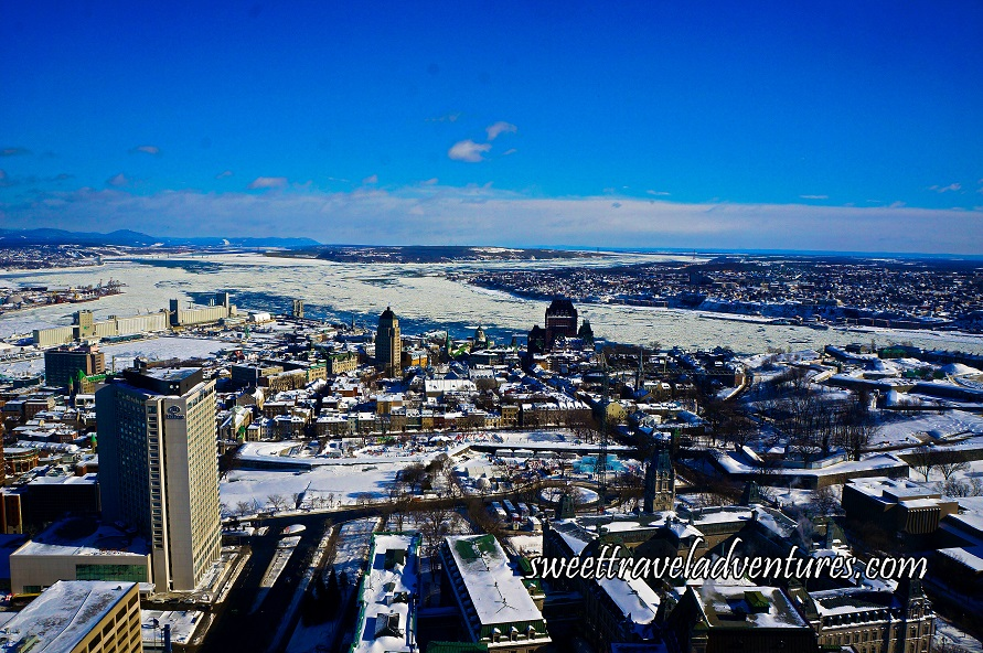 A Tall Brown Building on the Left and Other Buildings Around it, Many of Which Have Roofs Covered in Snow and the Ground is Covered in Snow, in the Distance is a River Going From the Left to Right and is Mostly Covered in Snow, Behind the River is More Buildings in the Distance and to the Left in the Distance is Mountains, there is a Blue Sky With a Lot of White Clouds on the Horizon