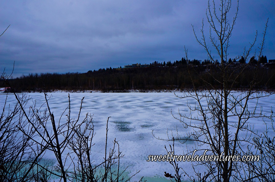 A Frozen River With a Few Bare Branches in Front, in the Background Many Trees and a House Elevated on a Hill, and a Cloudy Blue Sky