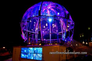 A Platform With a Giant Sphere at Night Lit Up With Purple Lights and Sparkly Stars Hanging Down From the Top of the Sphere, a Screen on the Front Side of the Platform, and Stairs Leading to the Platform on the Right