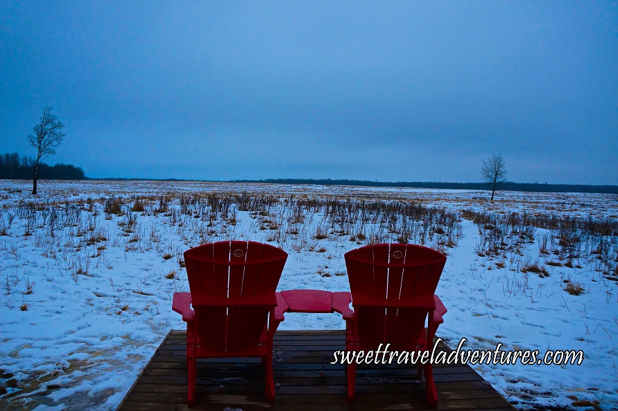 Two Red Chairs on a Wooden Platform Looking Out to a Snowy Field With a Single Bare Tree on the Right and Left and Trees in the Background and a Light Blue Sky